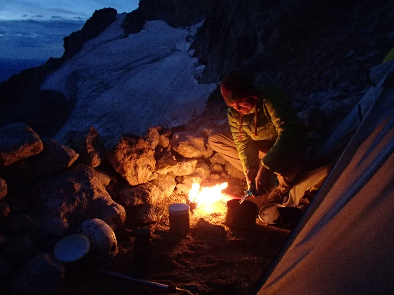 Ernie preparing an eraly morning breakfast with Middle Teton glacier in background